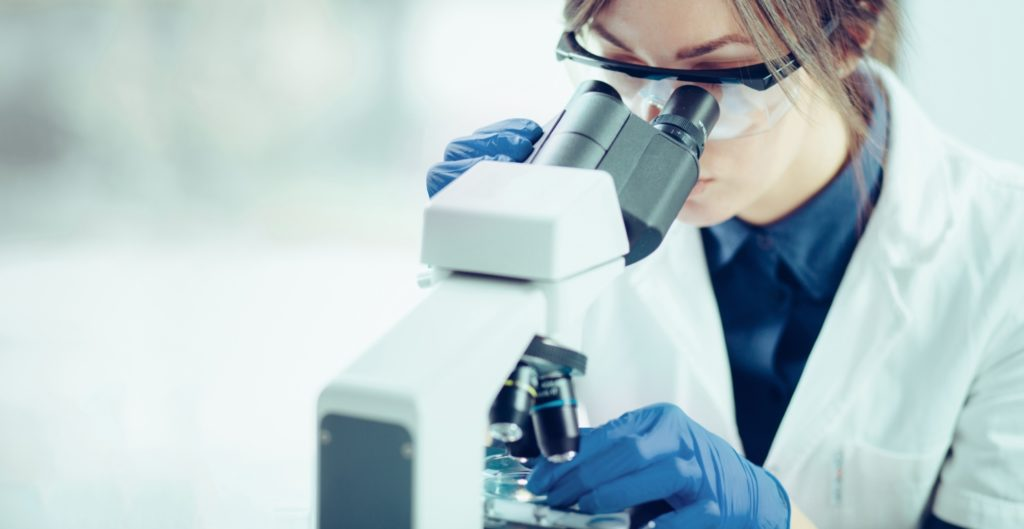 A scientist analyzing samples under the microscope
